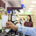 Pessoa-retirando-garrafa-de-vinho-da-gondola-em-um-supermercado.jpg